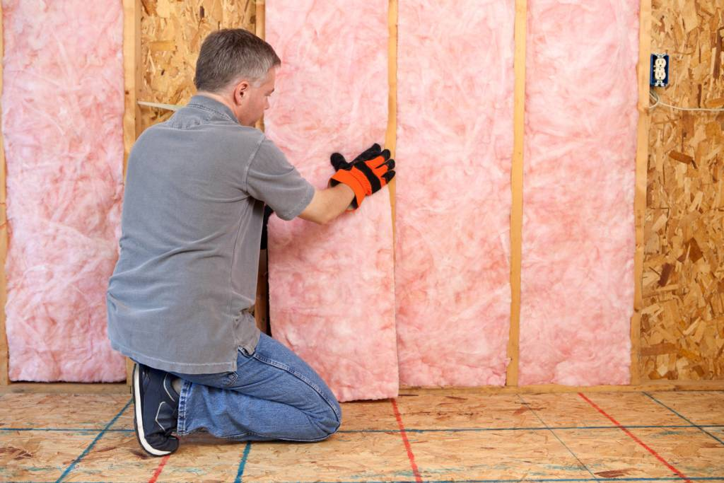 man insulating a basement
