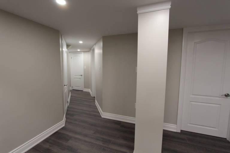 basement hallway with beige wall painting and baseboard trim - basement finishing contractors