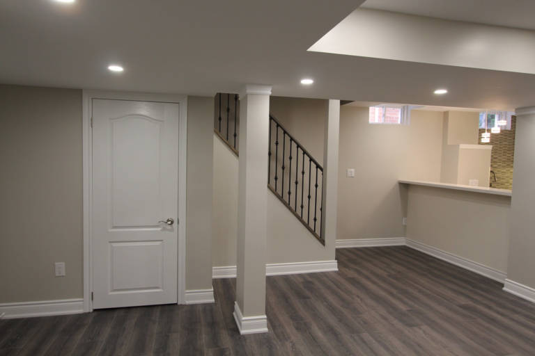 kitchen and living room with baseboard trim and wooden floor in luxury basement - basement renovations toronto