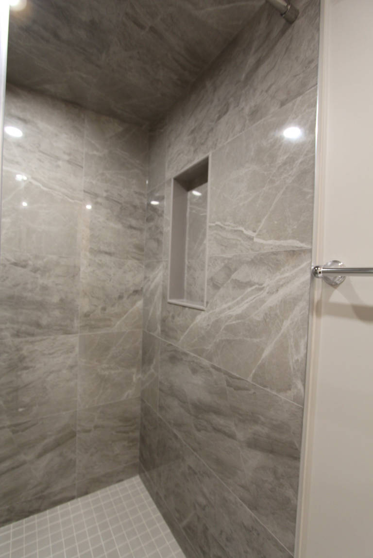 custom shower with build in storage space and marble tile wall decor - basement design