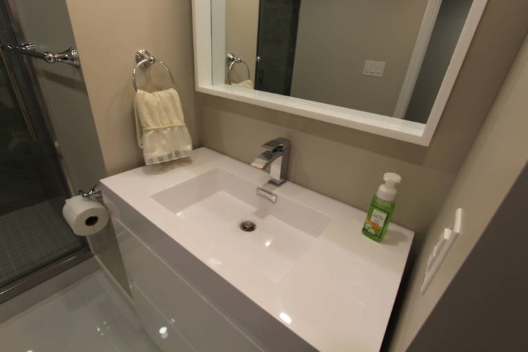 small bathroom with luxury pink and white vanity - basement renovation toronto