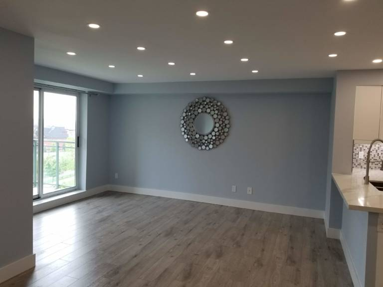 amazing living room with blue wall painting and baseboard trim in condo apartment - condo renovation
