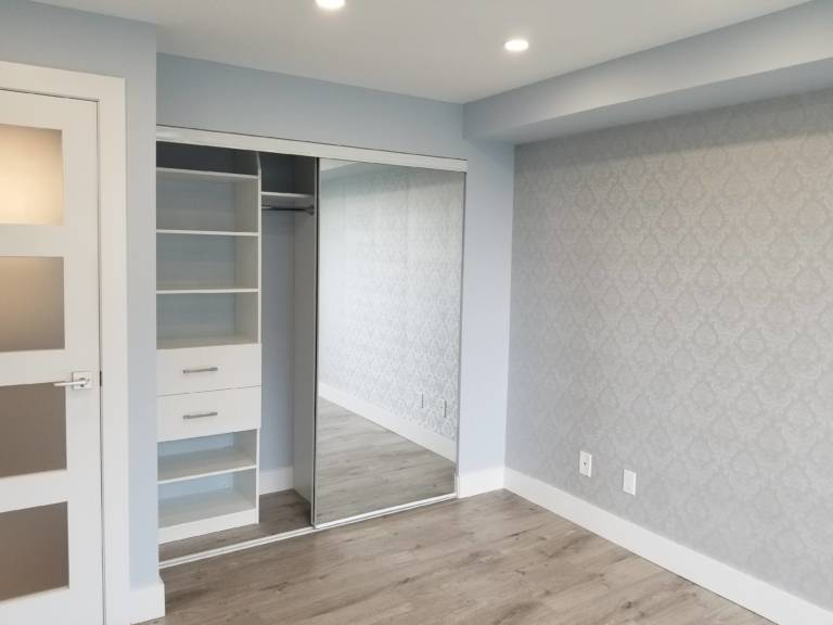 master bedroom in condo apartment with build in storage space and custom wallpaper - condo renovations toronto