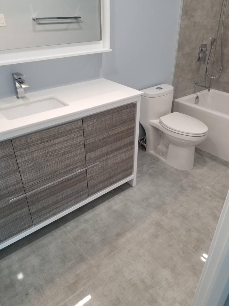 condo bathroom with white and brown vanity and custom bathtub - remodeling bathroom