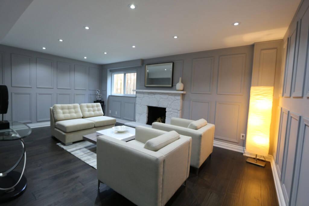 Modern Basement Family Room with Coffered Wall Decor - Basement Design Aurora